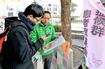 ドラベ症候群のてんかん発作を止める薬の早期承認を求める電子署名を呼び掛ける貞本さん(右)=26日、京都市下京区