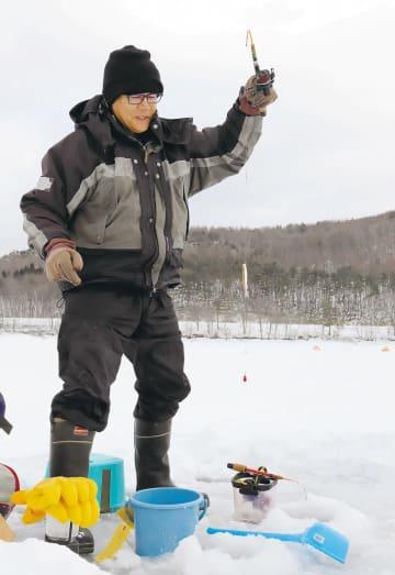 寒風吹きすさぶ中、ワカサギを釣り上げる愛好家