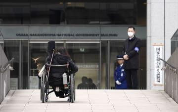 障害者を対象とした初の国家公務員試験の会場に車いすで向かう人=3日午前、大阪市の大阪中之島合同庁舎