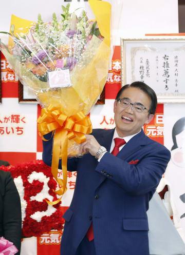 愛知県知事選で3選を決め、花束を手にする大村秀章氏=3日夜、名古屋市