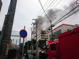 黒煙を上げて燃える市営住宅(中央奥)=3日午後0時50分ごろ、神戸市東灘区本山南町1