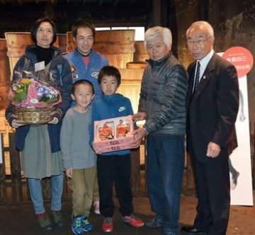 「金栗四三生家記念館」の1万43人目の来場者となり、金栗孝義さん(右から2人目)が作った記念品のイチゴを受け取る田之畑歩武君(右から3人目)=和水町