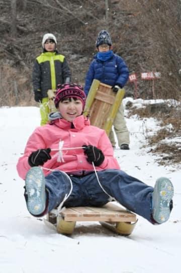 手作りのそりで雪の斜面を滑り降りる子どもたち