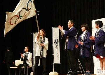 【五輪旗を振る田中理恵さん。左は松岡昌宏さん、右隣は仁坂吉伸知事(3日、和歌山市で)】