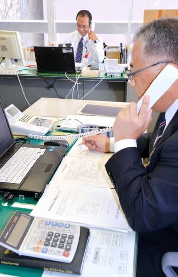市税滞納者へ電話で納付を呼び掛ける福井市の管理職=2018年11月8日、福井県の福井市役所