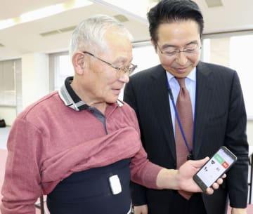 センサー付き肌着を試着する宮口友作さん(左)。スマートフォンには心拍数などが表示される=4日午後、福島県川俣町