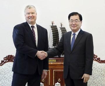 4日、韓国大統領府を訪問した米国のビーガン北朝鮮担当特別代表(左)と握手する鄭義溶・大統領府国家安保室長(韓国大統領府提供・共同)