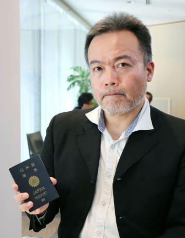 返納命令を受けた旅券を手にするフリージャーナリストの常岡浩介さん=4日午後、東京都港区