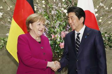 会談前に握手する安倍首相とドイツのメルケル首相=4日午後、首相官邸