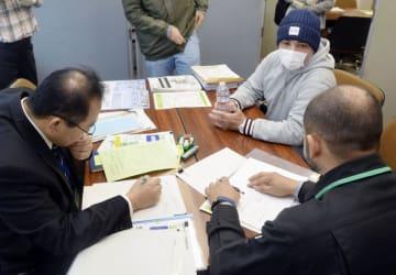 担当者から再就職先の紹介を受けるシャープ亀山工場の元作業員の男性(右奥)=4日、三重県鈴鹿市