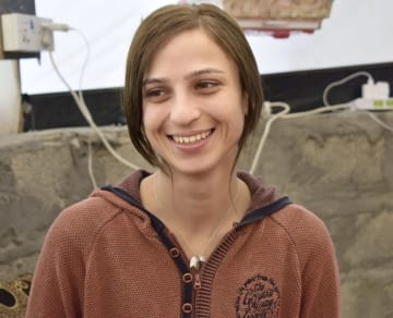 避難民キャンプで取材に応じ、ほほえむヤジド教徒のハラ・サフィールさん。胸のペンダントにはISに拘束された日にちを刻んでいる=2018年11月26日、イラク・ザホ(共同)