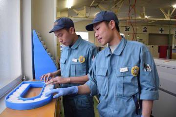 アイデアを出し合って生産工程の改善に取り組む三沢エンジニアリングのタップさん(右)とナムさん=1月、三沢市