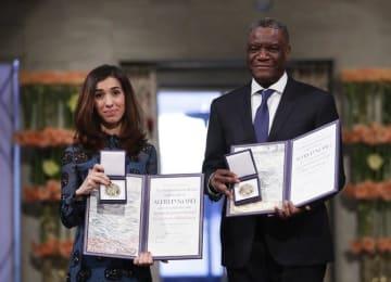 オスロで開かれた授賞式でノーベル平和賞を贈られたムクウェゲ氏(右)とムラド氏=2018年12月10日(AP=共同)