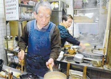 店で調理する菅原さん(左)と末子さん。長く守ったのれんを下ろす