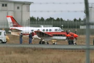 タイヤがパンクし、滑走路から外れた状態で停止した海上自衛隊のTC90練習機=5日午後5時49分、徳島空港