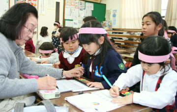 大分珠算連盟の中藪久美子会長(左)からそろばんを習う幼児ら=大分市の舞鶴公民館