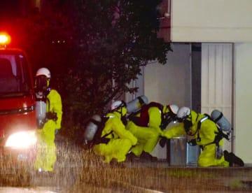 防護服を着た那覇市消防局の隊員らが薬品の処理に当たった=5日午後6時50分ごろ、那覇市の壺川市営住宅