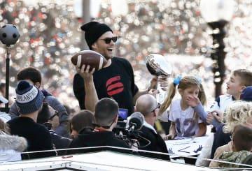 NFLスーパーボウルの優勝パレードで、トロフィーとボールを手に喜ぶペイトリオッツのQBブレイディ=5日、ボストン(AP=共同)