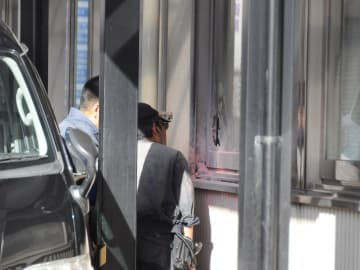 窓ガラスが割られた現場を確認する捜査員ら=2018年12月22日、那覇市前島・自衛隊沖縄地方協力本部