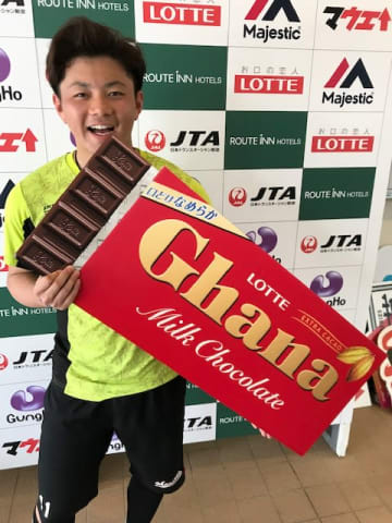 ガーナミルクチョコレートのパネルを手に笑顔の成田選手