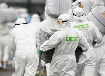 6日、豚コレラの陽性反応が出た愛知県豊田市の養豚場の周辺で防疫作業をする防護服姿の作業員