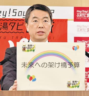 「未来への架け橋予算」と書かれたボードを掲げる村井知事