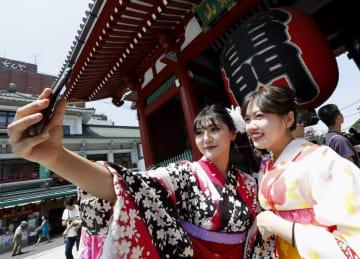 昨年7月、東京・浅草を訪れ、着物姿で記念撮影する外国人女性。左が韓国からの観光客