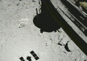 昨年10月、小惑星りゅうぐうの表面に約20メートルまで近づいた探査機「はやぶさ2」(右上)と探査機の影(左下)(JAXA提供)