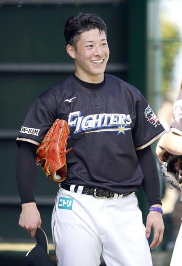 ブルペンでの投球練習を終え、笑顔を見せる日本ハム・吉田輝=2日、国頭