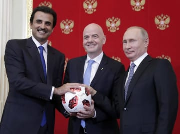 写真に納まるFIFAのインファンティノ会長(中央)。左は次回W杯開催国カタールのタミム首長、右はロシアのプーチン大統領=2018年7月15日、モスクワ(タス=共同)