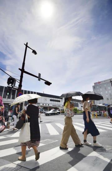 厳しい暑さとなった埼玉県の熊谷駅前を、日傘を差して歩く人たち=2018年8月2日