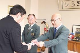 善意を小笠原市長に手渡す田中会長(右)