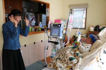 人工呼吸器を装着している大空ちゃん(右)と母親の光都子さん。中央にあるのが人工呼吸器とモニター=長崎市内