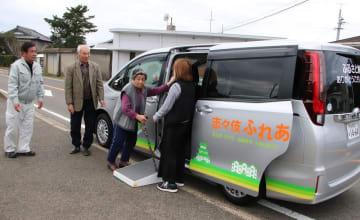 「志々伎ふれあい号」に乗車する1000人目の利用者、岩田さん(中央)=平戸市志々伎町