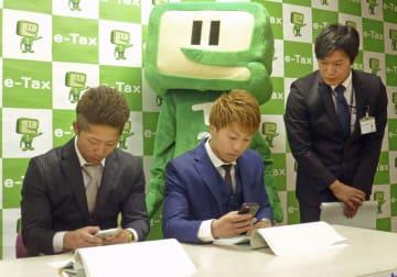 スマートフォンを使った税申告を体験するボクシングの(左から)井上拓真選手と兄の尚弥選手=7日午前、神奈川県大和市の大和税務署