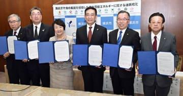 協定書を手にする野坂町長(右端)、林市長(左から3人目)ら=横浜市庁舎