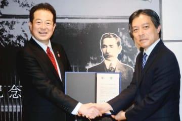 協定書に署名後、新宿区の吉住健一区長(右)と握手を交わす松山市の野志克仁市長=6日午後、東京都新宿区