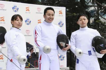 体験イベントで、初心者と対決後、笑顔でポーズをとる太田雄貴・日本フェンシング協会会長(中央)=7日、東京都渋谷区