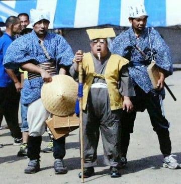 寸劇で演技する田中忠さん(右から2人目)=大分市内
