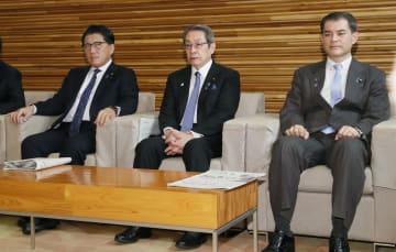 閣議に臨む石田総務相(中央)ら=8日午前、首相官邸