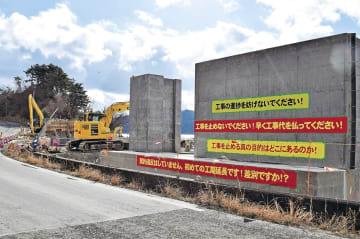 契約解除に抗議し、カルヤードが掲げた横断幕。周辺では重機が稼働している=石巻市雄勝町