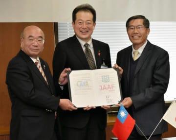 協定書を手に笑顔を見せる(左から)浜崎栄則副会長、野志克仁市長、盧瑞山会長=8日、松山市役所