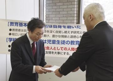 山口県教委の担当者に文書を手渡す「全国いじめ被害者の会」の大沢秀明代表(左)=8日午後、山口県庁