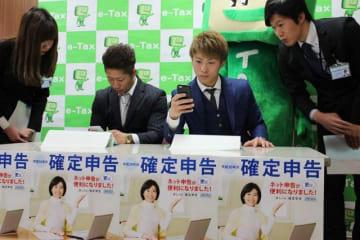 スマートフォンを使った確定申告の模擬体験をする井上尚弥選手(右2人目)と拓真選手(左2人目)=大和税務署