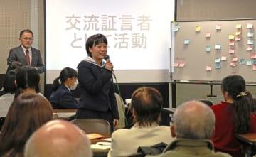 川崎さん(左奥)の前で意見発表する高校生=長崎市、県勤労福祉会館