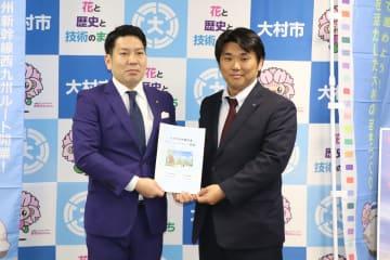 園田市長に素案を提出する田中委員長(右)=大村市役所