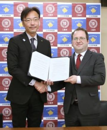 覚書を交わしたレオン・マラゾーグ駐日コソボ大使(右)と、国定勇人三条市長=8日、同市役所