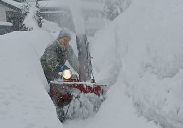 積雪で狭くなった歩道を雪まみれになりながら除雪する市民=8日午後、青森市幸畑3丁目