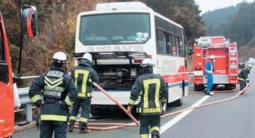 観光バスの消火活動をする消防隊員ら