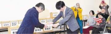 佐野副知事(左)に条例制定請求書を手渡す多々良代表